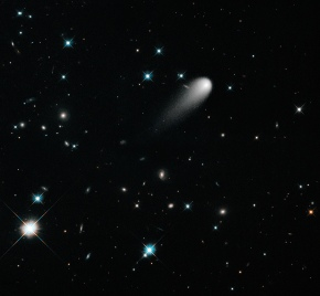 The sun-approaching Comet ISON floats against a seemingly infinite backdrop of numerous galaxies and a handful of foreground stars. The icy visitor, with its long gossamer tail, appears to be swimming like a tadpole through a deep pond of celestial wonders. In reality, the comet is much, much closer. The nearest star to the Sun is over 60,000 times farther away, and the nearest large galaxy to the Milky Way is over thirty billion times more distant. These vast dimensions are lost in this deep space Hubble exposure that visually combines our view of the universe from the very nearby to the extraordinarily far away. In this composite image, background stars and galaxies were separately photographed in red and yellow-green light. Because the comet moved between exposures relative to the background objects, its appearance was blurred. The blurred comet photo was replaced with a single, black-and-white exposure. The images were taken with the Wide Field Camera 3 on April 30, 2013. Credit: NASA, ESA, and the Hubble Heritage Team (STScI/AURA)