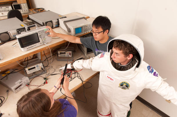 Kansas State engineering students work with a model spacesuit to explore the potential integration of wearable medical sensors. Credit: Kansas State University